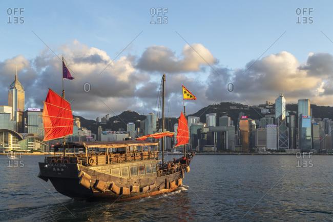 August 9, 2020: Junk boat and skyline of Hong Kong Island, Hong Kong, China, Asia