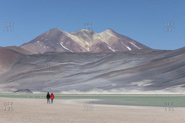 Couple walking in Salar de Aguas Calientes, Los Flamencos National Reserve, Antofagasta Region, Chile, South America