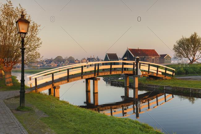 Wooden bridge over Zaan River at sunrsie, open-air museum, Zaanse Schans, Zaandam, North Holland, Netherlands, Europe