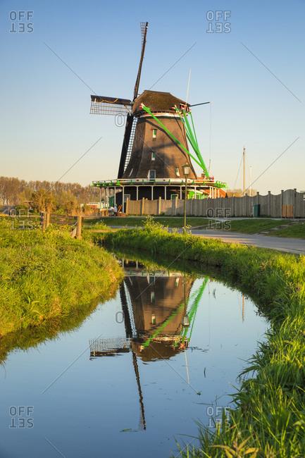 Windmill reflecting in a river, open-air museum, Zaanse Schans, Zaandam, North Holland, Netherlands, Europe