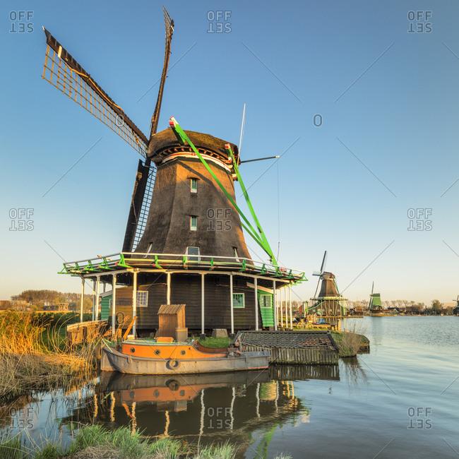 Windmill and boat on Zaan River, open-air museum, Zaanse Schans, Zaandam, North Holland, Netherlands, Europe
