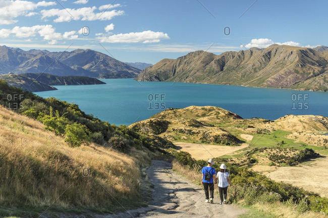 Hiker on Roy's Peak Track enjoying the view over Lake Wanaka, Mount-Aspiring National Park, Otago, South Island, New Zealand, Pacific