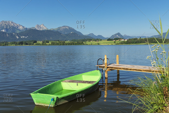 Rowing boat at a jetty, Hopfensee lake, Hopfen am See, Allgau Alps, Allgau, Schwaben, Bavaria, Germany, Europe