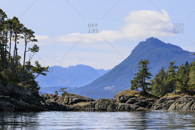 Tree lined rocky shore of an island in calm seas near Alert Bay, Inside Passage, British Columbia, Canada, North America, North America
