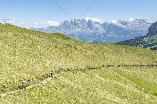 Mountain bikes and hikers on path at Duron Pass with the Odle group in background, Dolomites, Trentino-Alto Adige, Italy, Europe