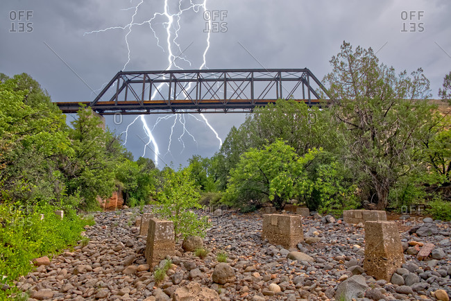 Lightning from a monsoon storm striking behind an old railroad trestle bridge that spans Bear Canyon near Perkinsville, Arizona, United States of America, North America