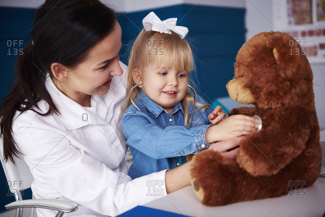 Doctor and girl examining teddy in medical practice
