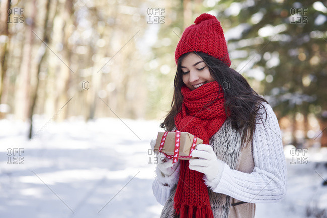 Portrait of happy young woman with Christmas gift in winter forest