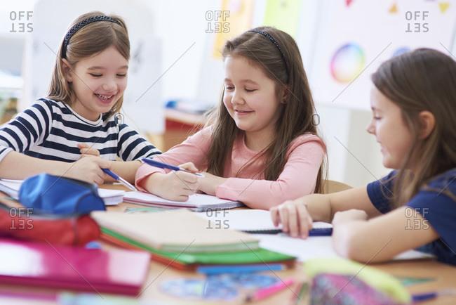 Happy schoolgirls working together in class