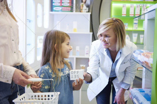 Pharmacist advising mother and daughter in pharmacy