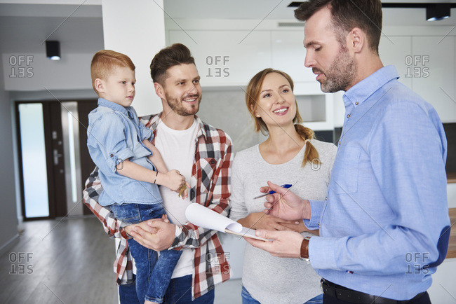 Family and real estate agent talking in new apartment