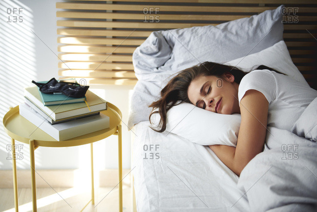 Portrait of woman sleeping in bed by daylight