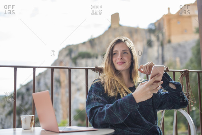 Spain- Alquezar- portrait of relaxed young woman with laptop and cell phone sitting on terrace