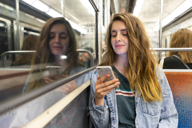 Smiling young woman in underground train looking at smartphone