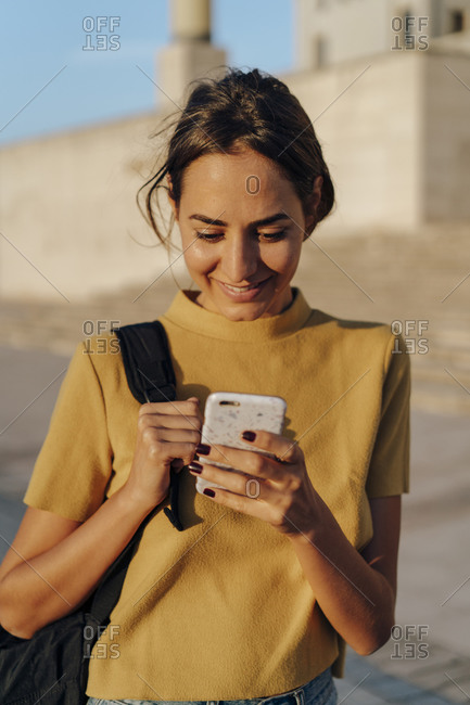 Smiling young woman looking at cell phone outdoors