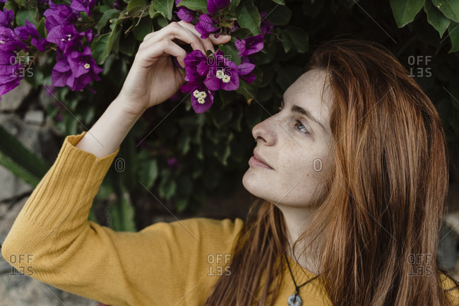 Spain- Canary Islands- Fuerteventura- profile of redheaded young woman with purple blossoms