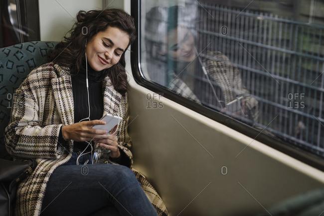 Young woman with earphones using smartphone on a subway