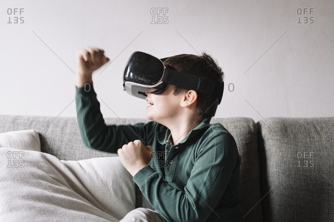 Boy sitting on the couch in the living room using Virtual Reality Glasses