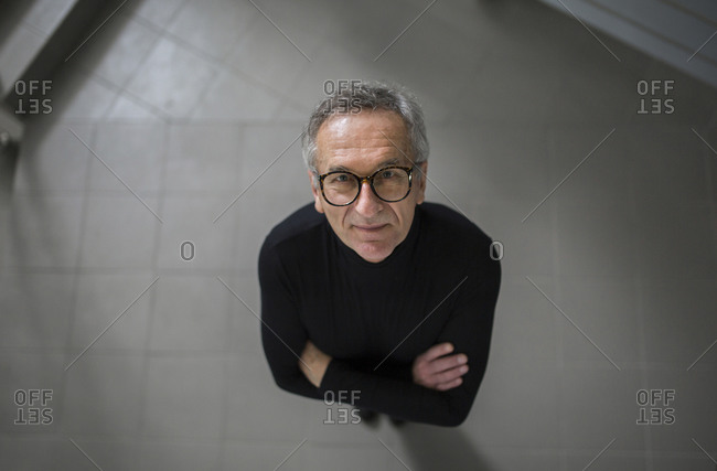 Smiling senior businessman looking up on office hallway