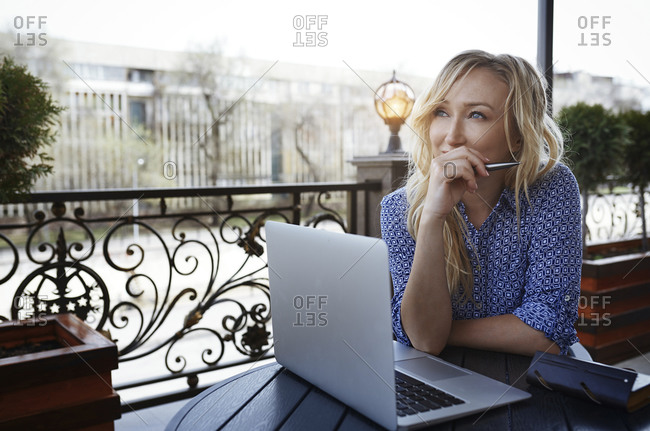 Female blogger working in coffee shop- using laptop
