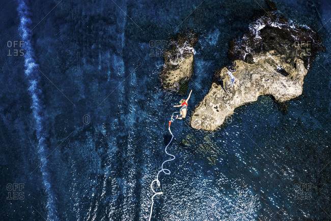 Greece- Crete- Bungee Jumping- woman jumping bungee over sea
