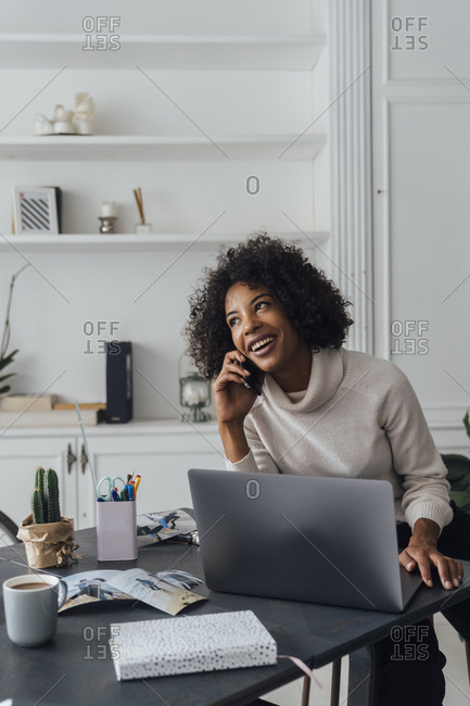Mid adult woman working in her home office- using smartphone