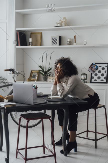 Freelancer sitting at her desk- daydreaming