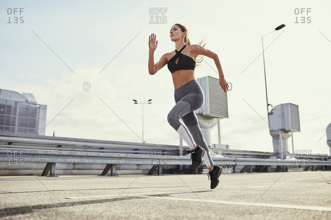 Young woman doing running exercises in the city