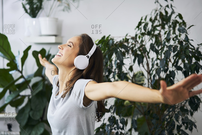 Happy young woman with outstretched arms listening to music at indoor plant