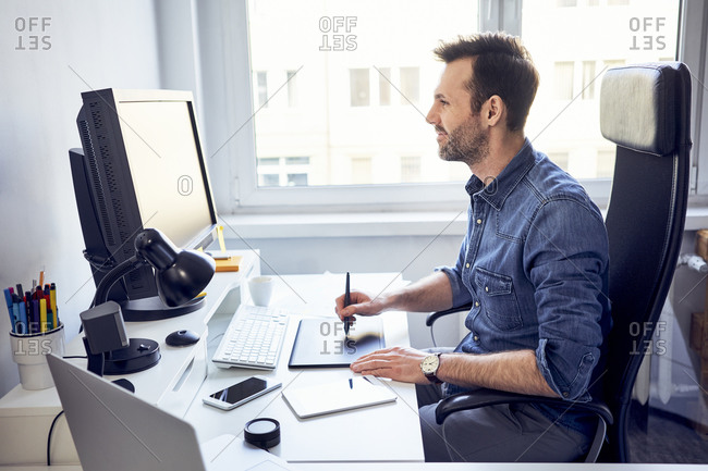 Smiling graphic designer working on computer at desk in office