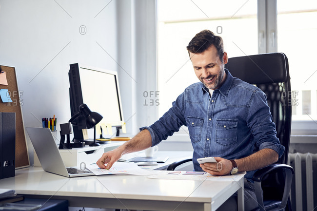 Smiling man with smartphone and draft working at desk in office