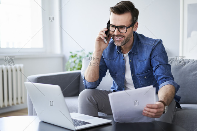 Smiling man with documents and laptop on sofa talking on cell phone