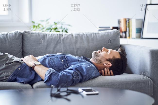 Relaxed man sleeping on sofa