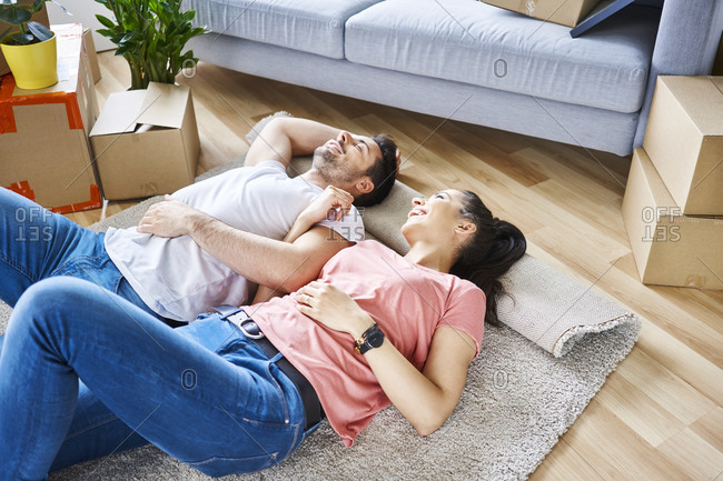 Happy couple relaxing while moving into new apartment