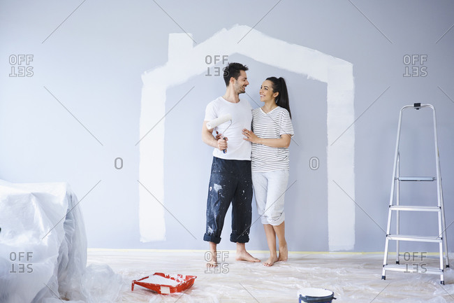 Happy couple painting in new apartment with house shape on wall