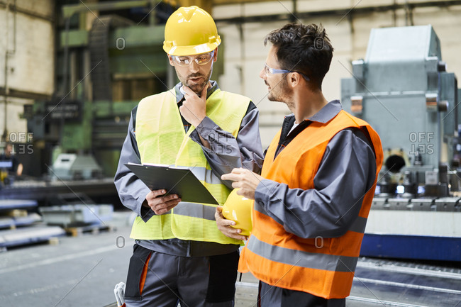 Two men wearing protective workwear holding clipboard and talking in factory