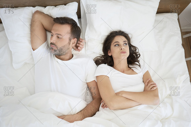 Frustrated couple lying in bed