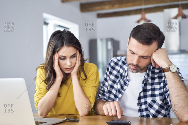 Worried couple sitting at dining table- using laptop- checking finances