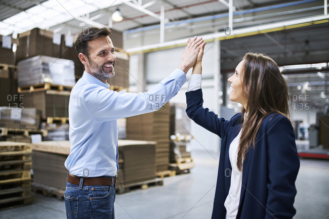 Businessman and businesswoman high fiving in a factory