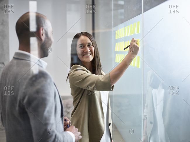 Businesswoman smiling at colleague writing on sticky notes at glass pane in office