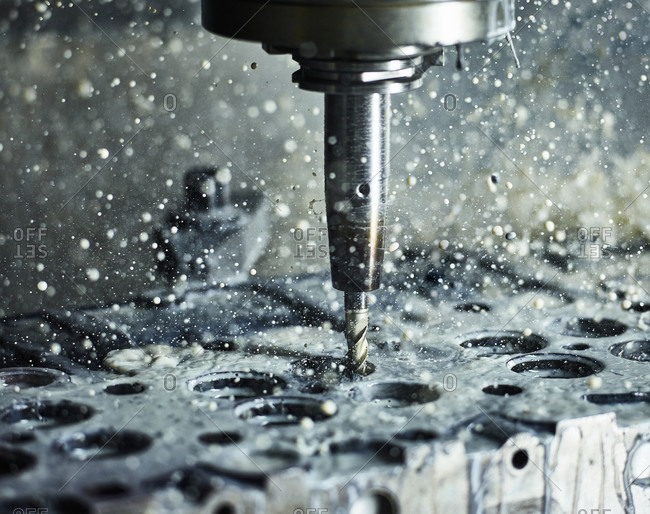 CNC machine drilling into cylinder head with coolant