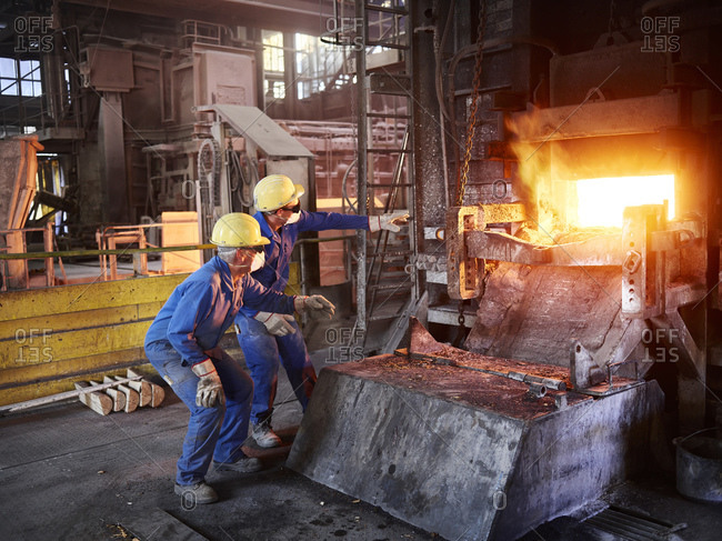 Industry- Smeltery: Workers checking blast furnace for fractures