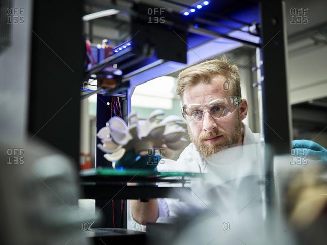 Technician looking at turbine wheel being printed in 3d printer