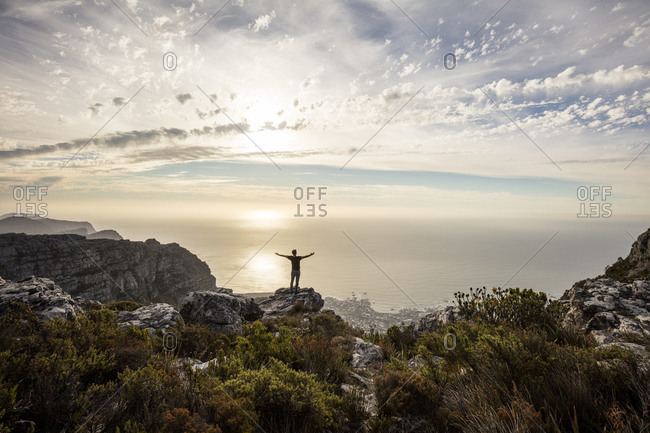 South Africa- Cape Town- Table Mountain- man standing on a rock at sunset