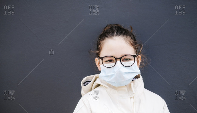 Girl with surgical mask in front of dark blue background