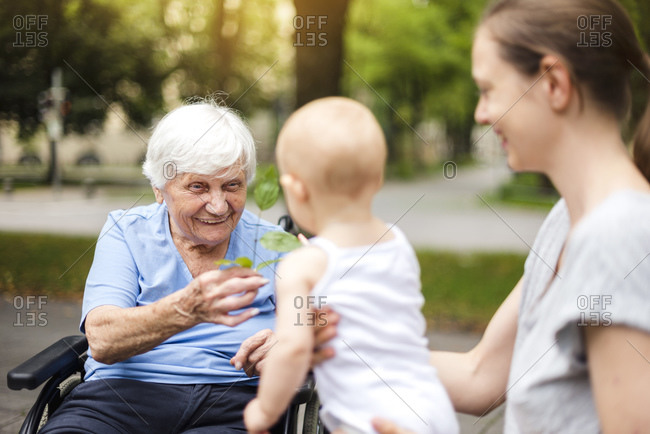 Portrait of happy senior woman with daughter and granddaughter in a park