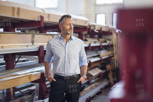 Mature businessman standing in factory storeroom looking sideways