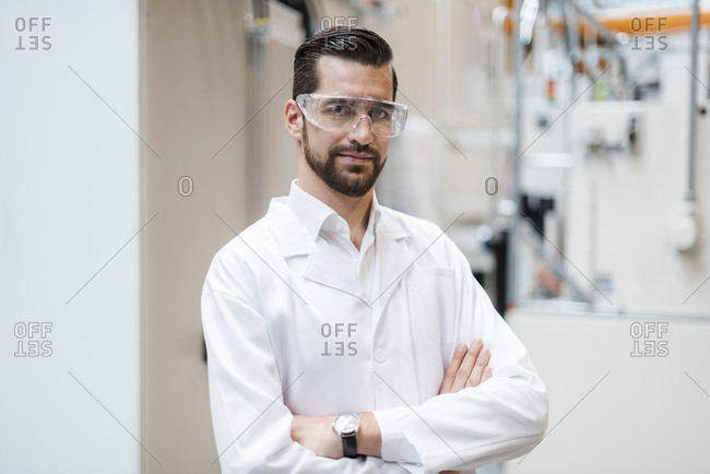 Portrait of man wearing lab coat and safety goggles in factory