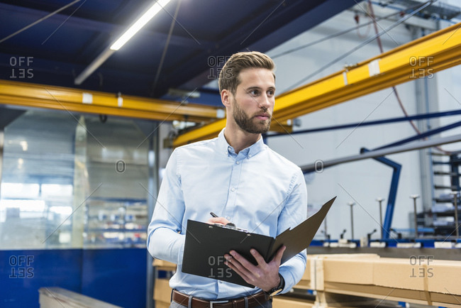 Young businessman with clipboard in production hall