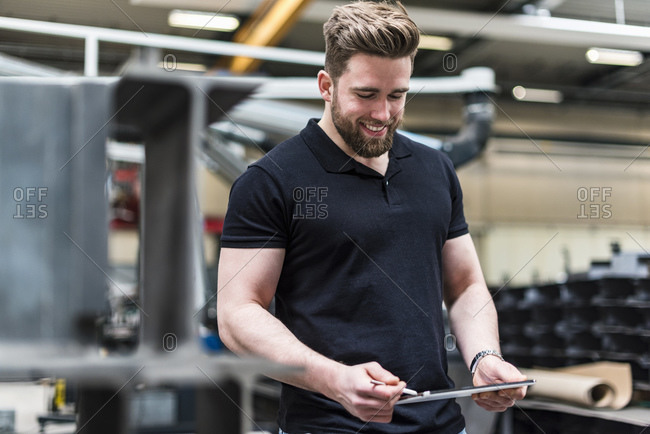 Smiling man with tablet standing on factory shop floor